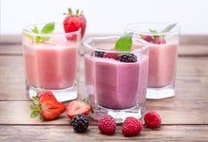 喝圆滑的人四个夏天草莓,黑莓,猕猴桃,在木桌上的莓 库存照片