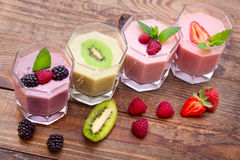 喝圆滑的人四个夏天草莓,黑莓,猕猴桃,在木桌上的莓 免版税库存照片