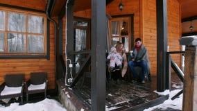 喝在一个美丽的房子的游廊的年轻家庭热的饮料 影视素材