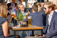 年轻喝在一个被包装的室外酒吧的商人和女实业家 免版税库存照片