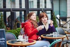 喝在一个巴黎人街道咖啡馆的两个快乐的女孩咖啡 免版税库存图片
