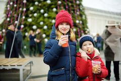 喝在传统圣诞节市场上的两个可爱的姐妹热的苹果汁 库存图片