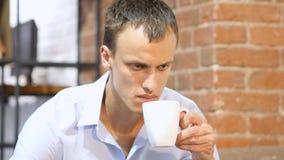 喝在创造性的工作区的年轻可爱的人一份咖啡 免版税库存图片
