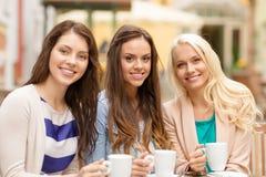 喝在咖啡馆的三个美丽的女孩咖啡 免版税库存图片