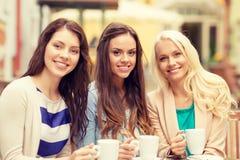 喝在咖啡馆的三个美丽的女孩咖啡 库存图片