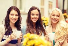 喝在咖啡馆的三个美丽的女孩咖啡 免版税库存照片