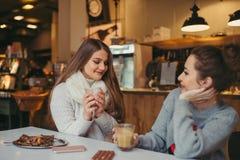 喝在咖啡馆的两个女孩咖啡 免版税库存照片