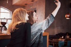 喝在咖啡馆的两个朋友咖啡,采取与一个巧妙的电话的selfies和获得做滑稽的面孔的乐趣 在的焦点 库存图片