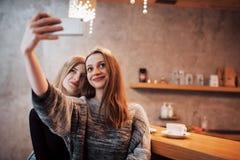 喝在咖啡馆的两个朋友咖啡,采取与一个巧妙的电话的selfies和获得做滑稽的面孔的乐趣 在的焦点 免版税图库摄影