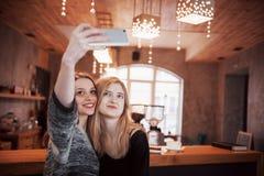 喝在咖啡馆的两个朋友咖啡,采取与一个巧妙的电话的selfies和获得做滑稽的面孔的乐趣 在的焦点 库存照片