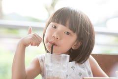 喝在咖啡馆的亚裔孩子 免版税库存照片