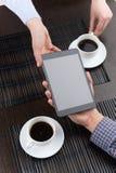 喝在咖啡馆的咖啡和显示新闻的朋友 免版税库存图片