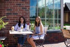 喝在咖啡馆的母亲和女儿一个鸡尾酒 免版税库存照片