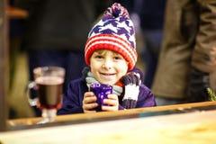 喝在圣诞节市场上的小孩男孩热巧克力 库存照片