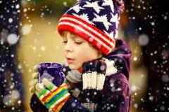 喝在圣诞节市场上的小孩男孩热巧克力 库存图片