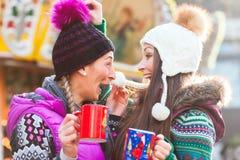 喝在圣诞节市场上的朋友蛋黄乳 库存图片