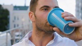 喝在城市都市生活方式的帅哥特写镜头画象可口咖啡 成功的商人雇员 影视素材