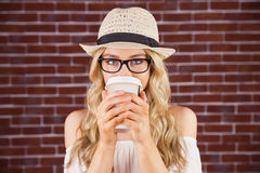 喝在外带的杯子外面的华美的白肤金发的行家 免版税库存图片