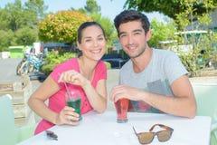 喝在外部咖啡馆桌上的夫妇 免版税库存照片