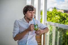 喝在大阳台的人一mojito 免版税库存照片