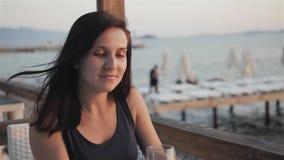 喝在室外大阳台的少妇红葡萄酒观看海的美好的日落视图 股票视频