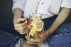 喝在家做的新鲜的夏天drin的少妇播种的射击 免版税库存图片
