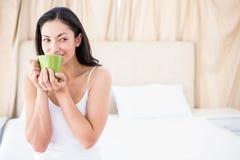 喝在床上的俏丽的浅黑肤色的男人热的饮料 免版税库存照片