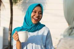 喝在房子和微笑前面的愉快的射击两hijab妇女的关闭茶 库存照片