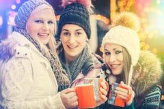 喝在杯子的妇女被仔细考虑的酒在德国圣诞节市场上 图库摄影
