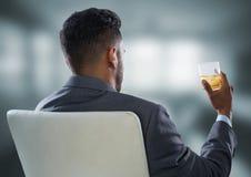 喝在模糊的灰色办公室的安装的商人 免版税库存图片