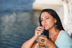 喝在海边咖啡馆的妇女被冰的咖啡 库存照片