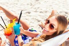 喝在海滩酒吧的朋友鸡尾酒 免版税库存图片