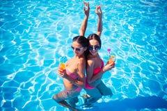 喝在游泳池的女孩鸡尾酒 免版税库存照片