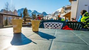 喝在滑雪胜地的温暖和鲜美咖啡 免版税库存照片