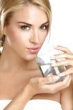喝在白色的年轻美丽的妇女淡水 图库摄影