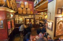 喝在老酒吧里面的许多顾客啤酒与葡萄酒桶和装饰 免版税库存照片
