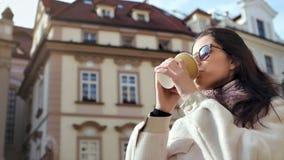 喝在背景低角度的微笑的美女热的饮料纸杯葡萄酒大厦 股票视频