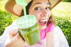喝在野餐的滑稽的妇女绿色戒毒所圆滑的人 室外面孔接近的画象 免版税库存照片