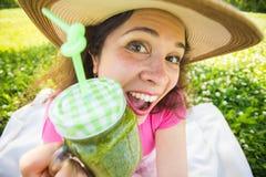 喝在野餐的滑稽的妇女绿色戒毒所圆滑的人 室外面孔接近的画象 库存图片