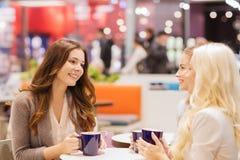 喝在购物中心的微笑的少妇咖啡 免版税图库摄影