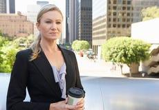 喝外带的咖啡在办公室外的女实业家 库存照片