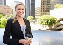 喝外带的咖啡在办公室外的女实业家 免版税库存图片