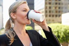 喝外带的咖啡在办公室外的女实业家 免版税库存照片
