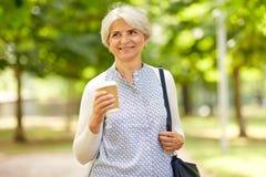 喝外带的咖啡的资深妇女在公园 免版税库存照片