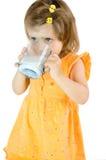 喝女孩少许牛奶 库存照片