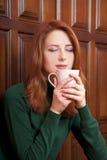 喝女孩的咖啡门在木头附近 免版税库存图片