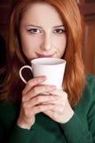 喝女孩的咖啡门在木头附近 库存照片