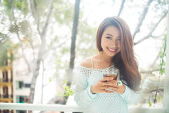喝她的早晨茶的一名年轻亚裔妇女的画象 落r 库存图片