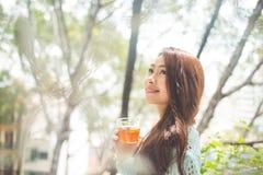 喝她的早晨茶的一名年轻亚裔妇女的画象 落r 库存照片