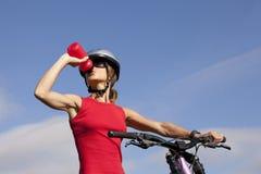 喝她的水妇女的自行车 免版税库存照片
